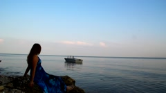 Lovely girl in a blue dress sitting  and looking into the distance on the boat Stock Footage