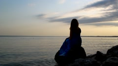 Lovely girl in a blue dress sitting and looking into the distance on sea Stock Footage