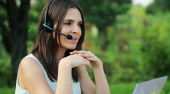 Beautiful female helpdesk working with laptop in the garden HD Stock Footage