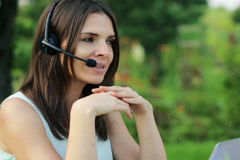 Beautiful female helpdesk working with laptop in  the garden NTSC Stock Footage