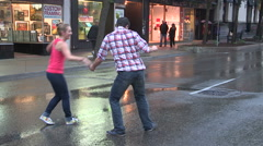 Swing dancing in the rain in the streets barefoot. Stock Footage