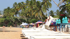 Man preparing sun beds for tourists on beach in Mirissa, Sri Lanka. Stock Footage