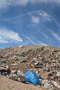 Illegal waste dump in the desert, mountains in the background against a blue  Stock Photos