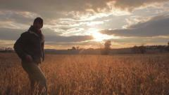 Farmer pauses and walks away from soybean field Stock Footage