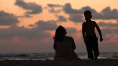 Mother with her baby during sunset on the sea Stock Footage
