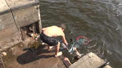 The young man pulls out a bike from the water. 4K. Stock Footage