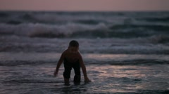 Little boy running in the sea in the evening Stock Footage