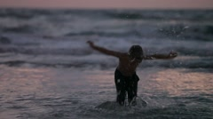 Little boy running in the sea in the evening. ashdod. israel Stock Footage