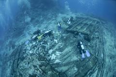 Scuba divers exploring the shipwreck debris on the ocean floor Stock Photos