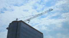 Stock Video Footage of Top of skyscraper and construction crane, clouds moving