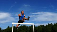 Sprinter in hurdling in track and field Stock Footage