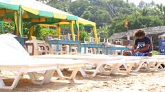 Stock Video Footage of Man preparing sun beds for tourists on beach in Mirissa, Sri Lanka.