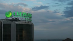 Illuminated signboard of Sberbank on background of cloudy evening sky Stock Footage