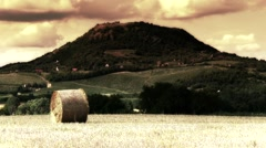 Hay Bale on Harvested Grain Field and Volcanic Hill 1 stylized Stock Footage