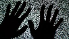 Male hands crawling up the TV screen with static television noise as background. Stock Footage