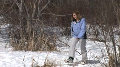 WOMAN SNOWSHOEING IN WOODS Stock Footage