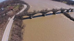 High and Fast Moving River flowing past deteriorating abandoned bridge aerial. Stock Footage
