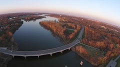 Aerial shot of traffic crossing river on bridge over reflective calm river Stock Footage