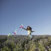 A child, a girl running with a paper streamer fluttering in the wind. Stock Photos