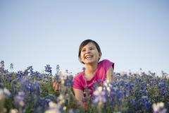 A young girl sitting in a field of wild flowers, laughing. Stock Photos
