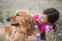 a young girl hugging a golden retriever pet. - stock photo