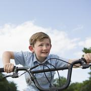 A young boy leaning over the handlebars of a bicycle. Stock Photos