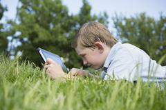 A young boy lying on the grass, using a digital tablet. Stock Photos