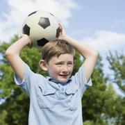 a young boy holding a soccer ball above his head. - stock photo