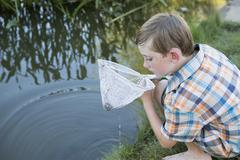 A young boy outdoors with a fishing net, examining the objects in the net, on Stock Photos
