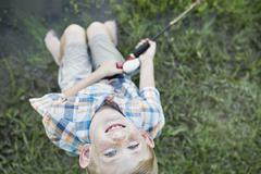 A young boy outdoors looking upwards. Stock Photos