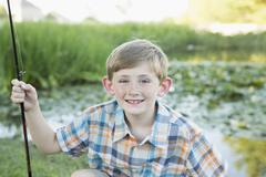 A young boy with his fishing road, by a lake or river. Stock Photos