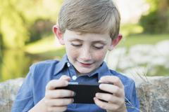 A young boy outdoors sitting leaning against a rock, using a handheld electro Stock Photos