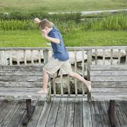 A young boy outdoors leaping from one bench to another on a jetty over water. Stock Photos
