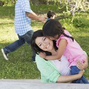 A mother in the park with her daughter, laughing and kissing each other. fath Stock Photos