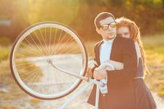 young stylish guy with girl and the bicycle outdoors - stock photo
