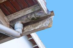 Moldy and flaking asbestos guttering and downpipe Stock Photos