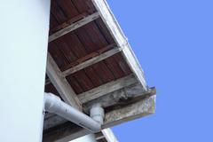 peeling asbestos guttering in need of maintenance - stock photo
