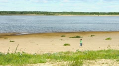 Lonely child walking along the shore of a large river Stock Footage