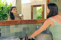 Woman brushing hair in bathroom and drinking coffee Stock Footage