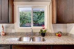 kitchen cabinet with sink and window view - stock photo