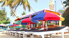 Stock Video Footage of View of sun beds and parasols lined up on sandy beach in Mirissa, Sri Lanka.