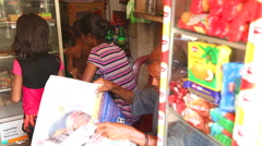 Stock Video Footage of MIRISSA, SRI LANKA - MARCH 2014: Family in local convenience store.