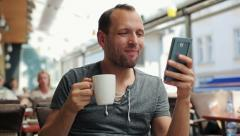 Happy man with smartphone sitting in the restaurant HD Stock Footage