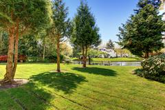 Residential complex backyard garden with pond, trees and sitting areas Stock Photos