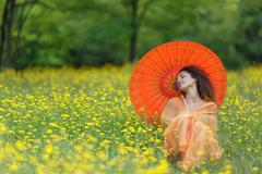 Beautiful elegant woman with an orange parasol Stock Photos