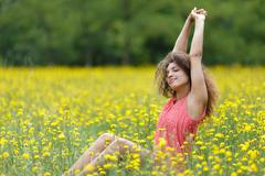 beautiful young woman stretching with pleasure - stock photo