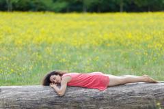 Beautiful young woman sleeping on a log Stock Photos