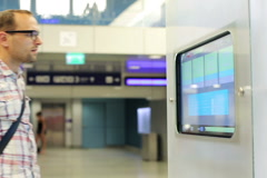 Young man using touch screen info in the station NTSC Stock Footage