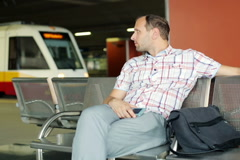 young, impatient man waiting in the train station NTSC - stock footage