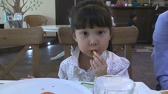 Young Asian girl eating a french fry Stock Footage